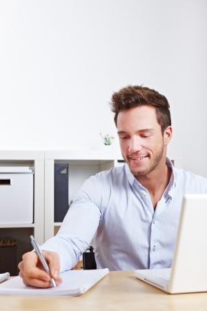 taking note: Studente di college di apprendimento con il computer e prendere appunti