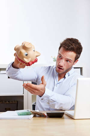 Shocked university student shaking empty piggy bank at desk photo