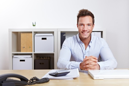 merchant: Smiling business consultant in office at desk