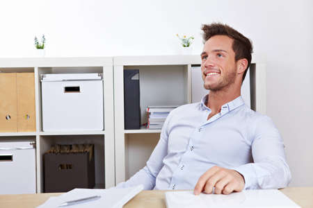 lean back: Happy business man relaxing in office at desk leaning back