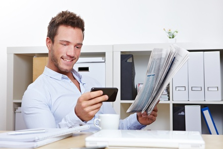 Young business man in office looking for job with smartphone and newspaper photo