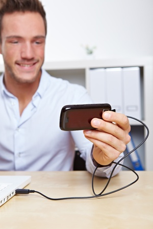 Young business man downloading images from cell phone to computer via USB photo