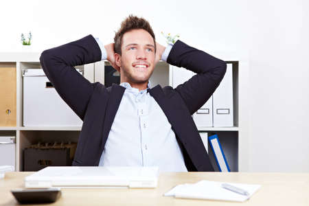 Pensive happy business man in office relaxing with hands behind his head photo