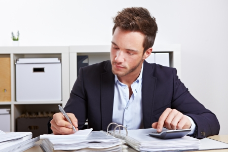 examiner: Business man working with calculator and files in office