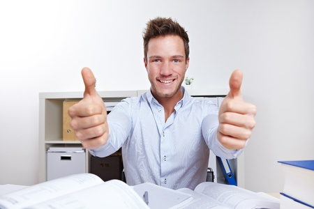 Cheering college student learning with books holding thumbs up Stock Photo - 12361594