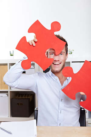 Happy business man cheering with oversized jigsaw puzzle pieces in office photo