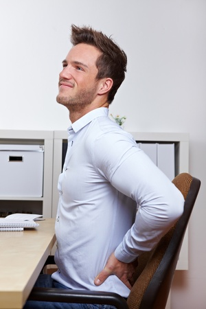 lean back: Business man with back pain in office chair at desk Stock Photo