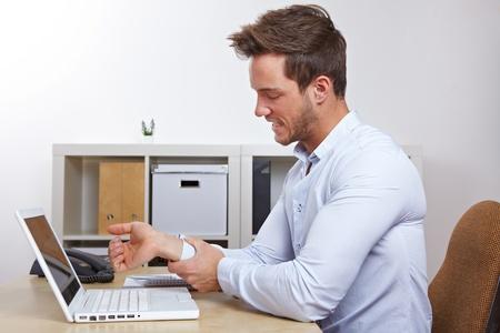 douleur main: Homme d'affaires dans le bureau avec le syndrome RSI tenant sa main endolorie Banque d'images
