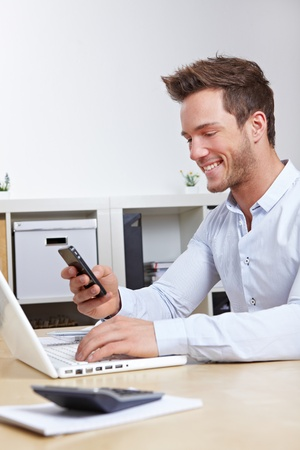 Business man connecting cell phone and computer wireless via bluetooth in office Stock Photo - 12361605