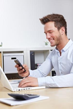 calling: Hombre de negocios de conexi�n m�vil y radio de la computadora a trav�s de bluetooth en la oficina