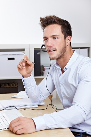 Support hotline call-agent working in call center with headset photo
