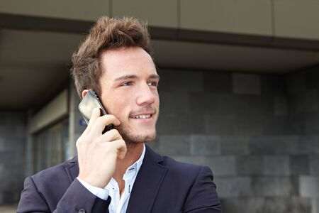 servicing: Young business man making cell phone call in urban city