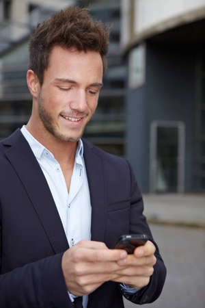 Business man on the run in city checking cell phone for new messages photo