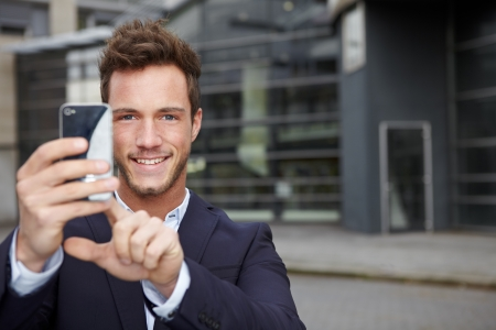 Happy business man taking pictures with smartphone in city photo