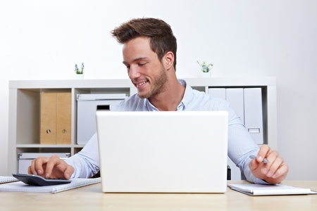 Business man working with laptop and calculator in office photo
