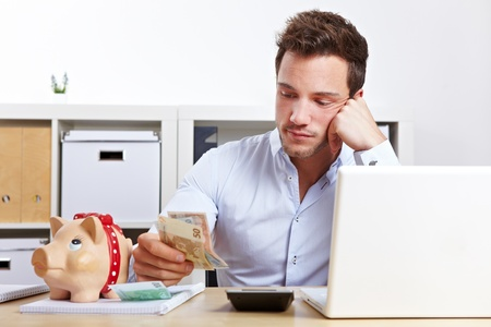 worry: Worried business man with money and piggy bank in office