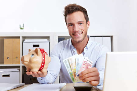 Happy business man with piggy bank and money in office photo