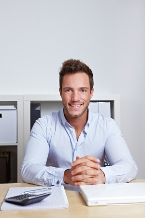 Smiling attractive business man sitting in office at desk photo