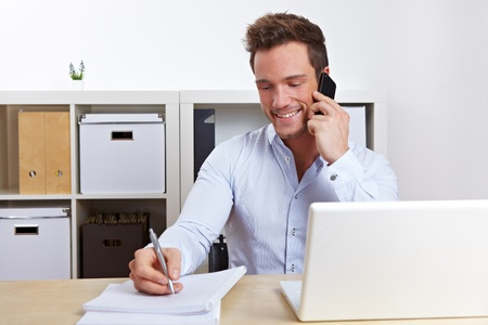 Smiling business man using cell phone at desk in office photo