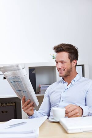 Young business man in office reading the appointments section in newspaper photo