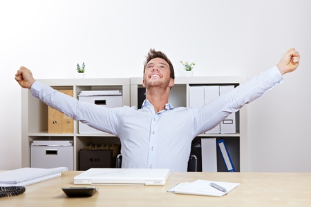 joyfulness: Happy successful business man cheering with clenched fists in office