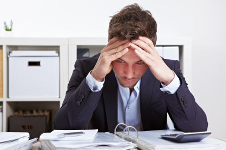 office chaos: Business man in office with burnout syndrome at desk Stock Photo
