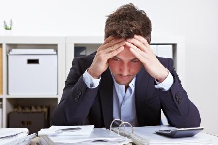 hombre preocupado: Hombre de negocios en el cargo con el s�ndrome de burnout en el escritorio