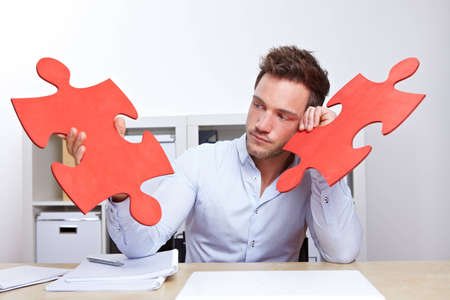 Pensive business man with two oversized red jigsaw puzzle pieces in office photo