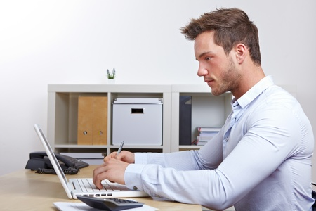 Business man working with laptop computer in office at desk photo