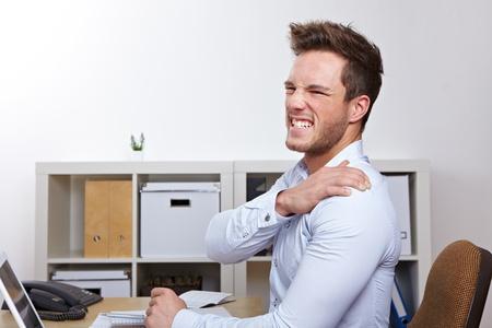 dolor de espalda: Hombre de negocios con el dolor de hombro en el cargo en el escritorio