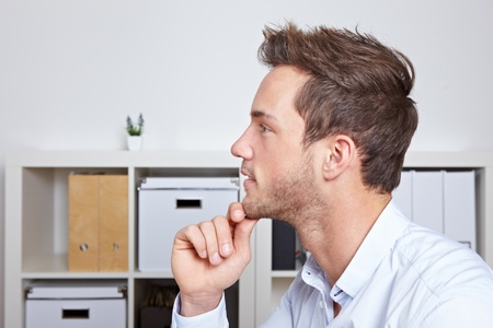 man face profile: Young business man in profile view with hand on chin in office