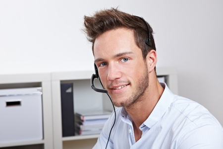 hear business call: Helpful phone support agent with headset in callcenter office Stock Photo
