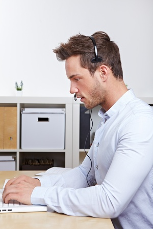 Telemarketing employee with headset working with laptop in office