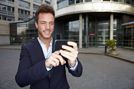 Business man using navigation app in smartphone in urban city photo
