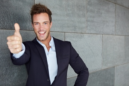 congratulations: Happy business man in urban city holding thumbs up Stock Photo