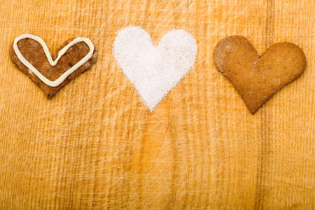 Different cookie hearts with sugar on wooden board photo