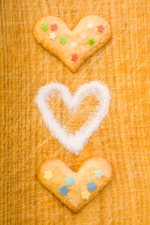 Different hearts and sugar on a wooden cutting board photo