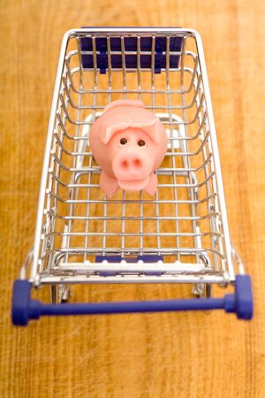 Marzipan pig in shopping cart looking up Stock Photo - 12856193