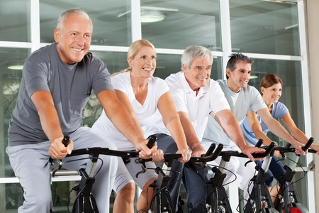 senior citizens: Happy senior citizens exercising in spinning class in fitness center Stock Photo
