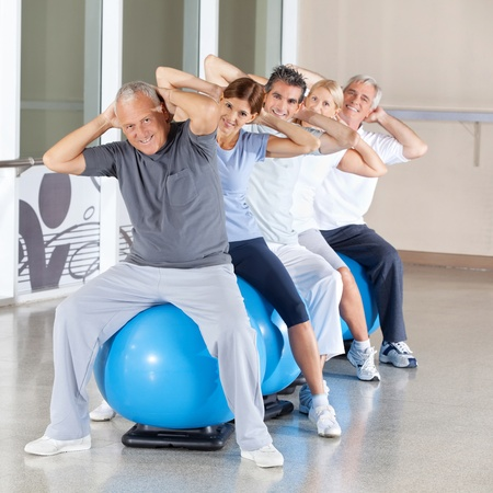 muscle formation: Happy senior citizens doing back exercises on gym ball in fitness center