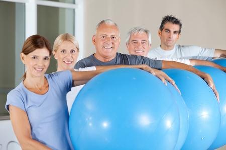 Happy senior citizens holding blue gym balls in fitness center Stock Photo - 12953281