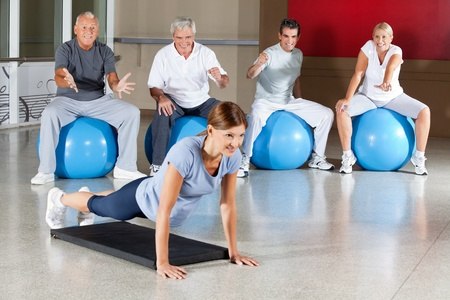 Senior group motivating woman in gym who does push ups Stock Photo - 12953819