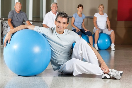 Happy man sitting with blue gym ball in fitness center with senior group Stock Photo - 12954017