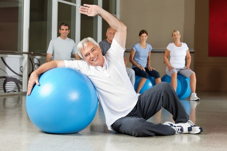 muscle formation: Elderly man doing back exercises with gym ball in fitness center