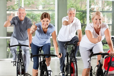 sit up: Senior group on spinning bikes in gym holding thumbs up