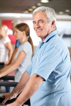 Elderly man exercising on fitness treadmill in gym photo