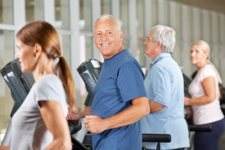 Happy senior citizens jogging on treadmills in gym photo