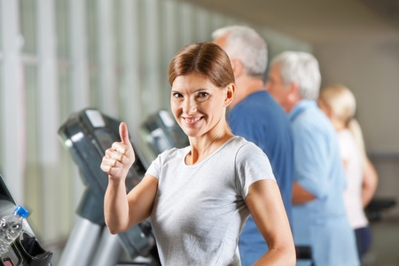 Smiling elderly woman on treadmill holding thumb up in fitness center photo