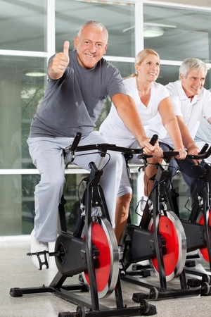 home gym: Happy senior man on spinning bike holding thumbs up in gym Stock Photo