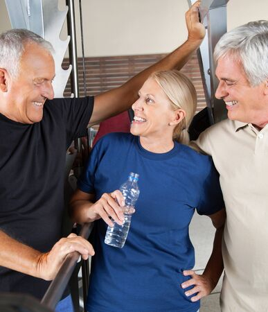 Three senior people talking in gym while having a break photo